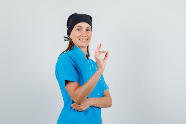 Ärztin zeigt ok zeichen in blauer uniform, schwarzem hut und sieht fröhlich aus. vorderansicht.