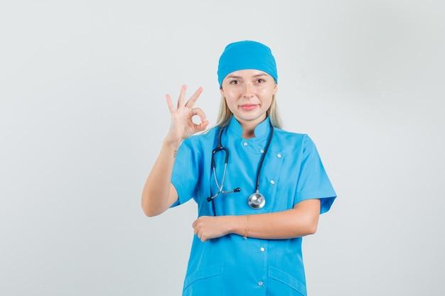 Ärztin zeigt ok zeichen in blauer uniform und sieht zufrieden aus.