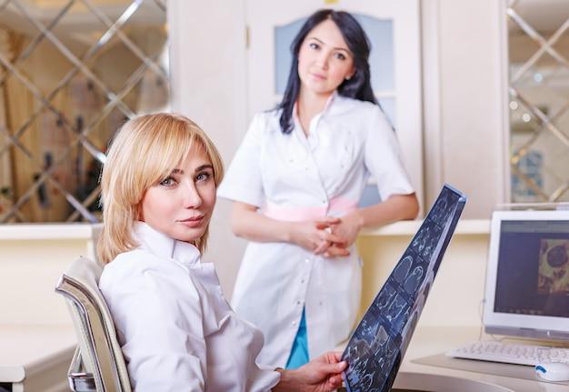 Ärztinnen, die einen tomographie-röntgenstrahl betrachten