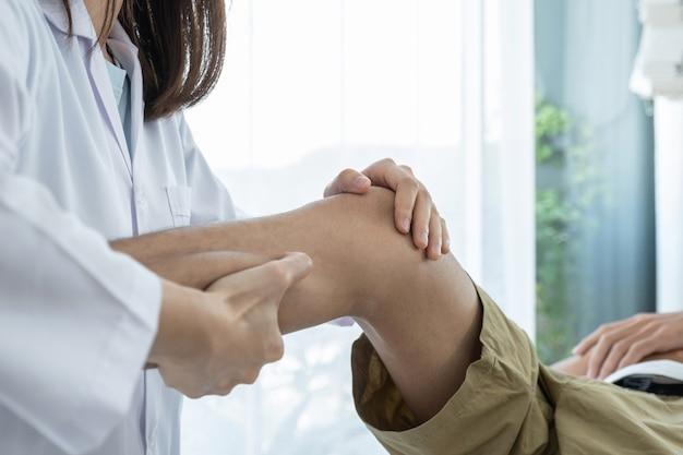 Ärztinnen hände, die physiotherapie machen durch strecken des beins und des knies eines männlichen patienten.