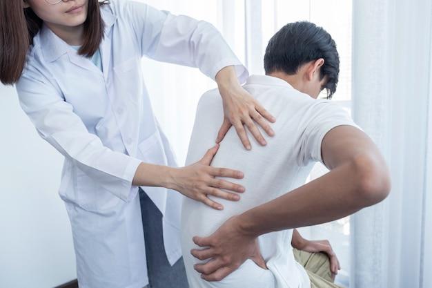 Ärztinnen hände machen physiotherapie durch verlängerung des rückens eines männlichen patienten.