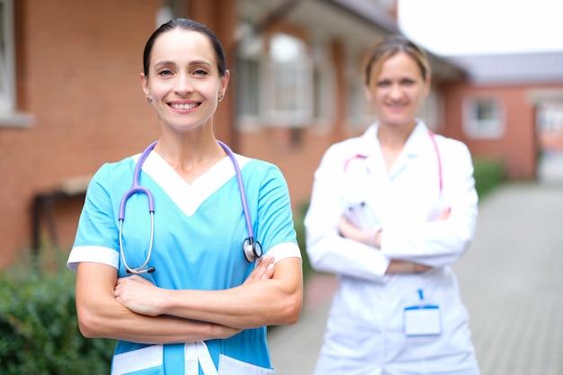 Ärztinnen in uniformen stehen in der nähe der klinik