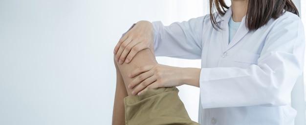 Ärztinnen machen physiotherapie durch streckung von bein und knie eines männlichen patienten.