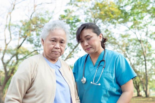 Ärztliche hilfe und pflege asiatische ältere frau beim gehen im park.