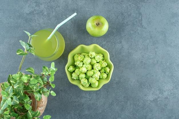 Ästhetische anordnung von popcornschüssel, glas apfelsaft, einzelnem apfel und einem eingewickelten wase mit einer dekorativen pflanze auf marmorhintergrund. foto in hoher qualität