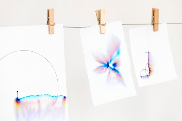Ästhetische chromatographiekunst auf weißem papier, das an einem seil hängt