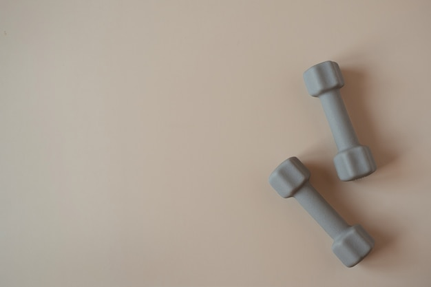 Ästhetische kreative flachhanteln für yoga, fitness, trainingstraining auf neutralem beige