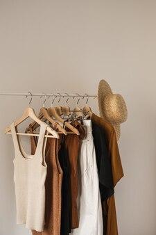 Ästhetische minimalistische mode-influencer-blog-komposition. stilvolle pastellfarbene sommerkleidung für frauen, kleid, tops, t-shirts, strohhut auf kleiderständer gegen weiße wand