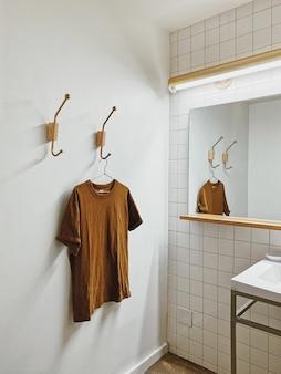 Ästhetische vertikale aufnahme eines weißen raumes mit hölzernem innenmaterial und t-shirt