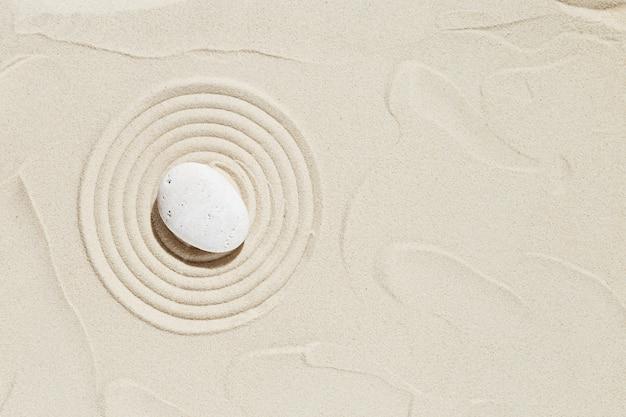Ästhetischer minimaler hintergrund mit zen-stein auf sandmuster im japanischen zen-garten