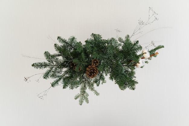 Ästhetisches design für weihnachten mit hängender girlande aus kiefernnobilis, lokalisiert auf weiß.