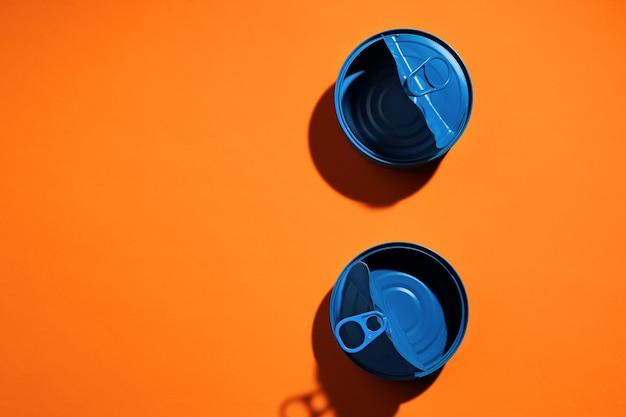 Ästhetisches konzept mit blau lackierter blechdose auf orangefarbener oberfläche