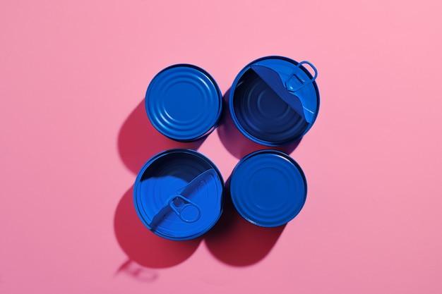 Ästhetisches konzept mit blau lackierter blechdose auf rosa oberfläche