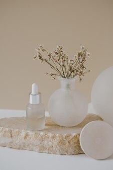 Ästhetisches minimalistisches schönheitspflege-therapiekonzept. bio-serumöl-kosmetikflasche auf stein mit blumen gegen neutrales beige