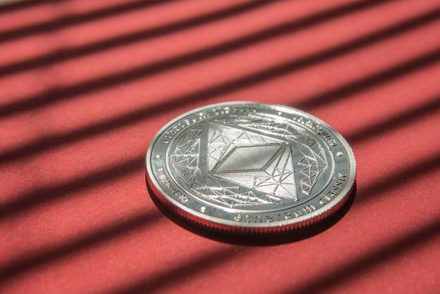 Äther. kryptowährung ethereum. e-währung ethereum auf hintergrund des roten hintergrundes