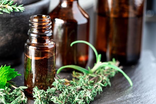 Ätherische öle in einer braunen glasflasche, thymian, rosmarin und minze auf dem tisch. ätherisches kräuteröl, aromatherapie. kategorie lebensstil