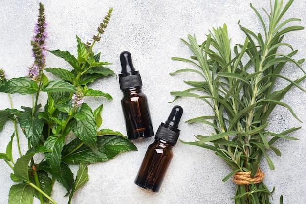 Ätherisches aromaöl in dunklen glasflaschen mit pfefferminze und rosmarin