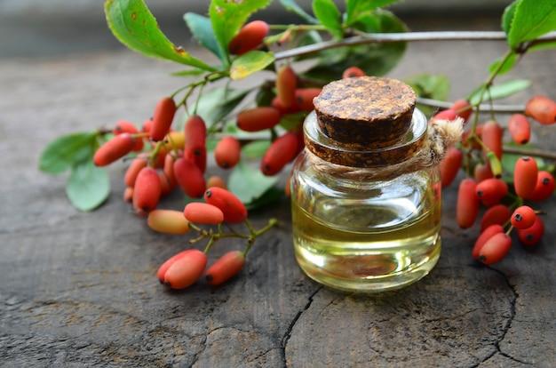 Ätherisches berberitzenöl in einer glasflasche auf altem holztisch für aromatherapie-hautpflege oder spa berberis vulgaris kräuterextrakt
