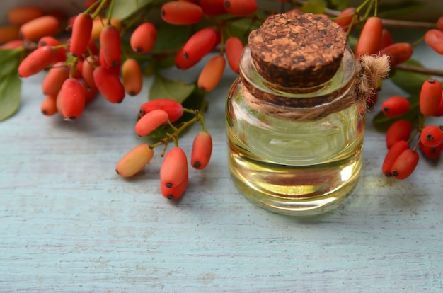 Ätherisches berberitzenöl in einer glasflasche auf altem holztisch für aromatherapie-hautpflege
