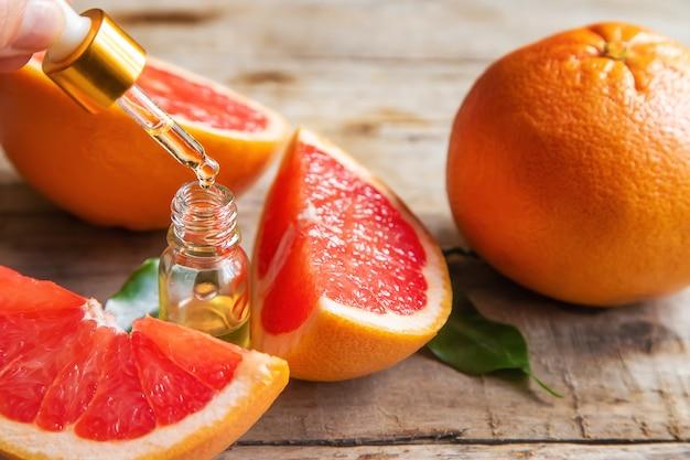 Ätherisches grapefruitöl in einer kleinen flasche. selektiver fokus. essen.