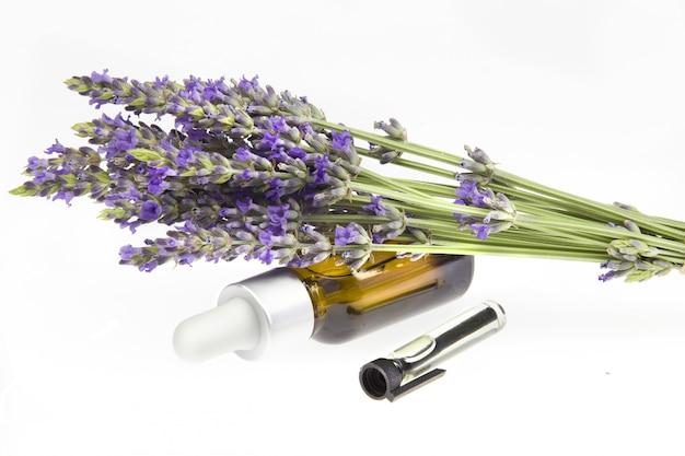 Ätherisches lavendelöl in der flasche mit tropfenzähler auf weißem schreibtisch. horizontale nahaufnahme