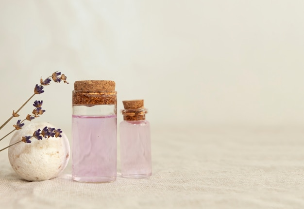 Ätherisches lavendelöl mit getrocknetem lavendelbouquet auf dem leinenstoff.