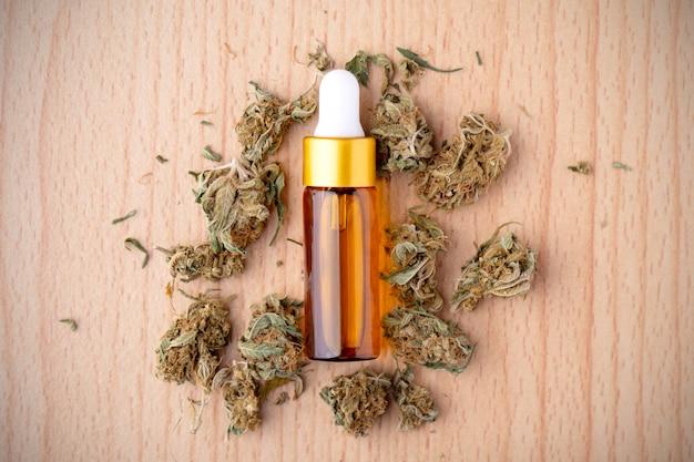 Ätherisches öl aus medizinischem cannabis. marihuana auf holztisch