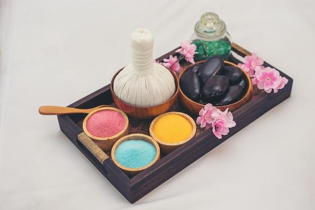 Ätherisches öl, badesalz und schwarze massage heiße steine. spa-salon-konzept