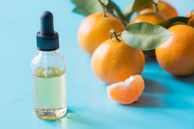 Ätherisches öl der orange mandarine in der glasflasche über blauem pastellhintergrund. hautpflege .