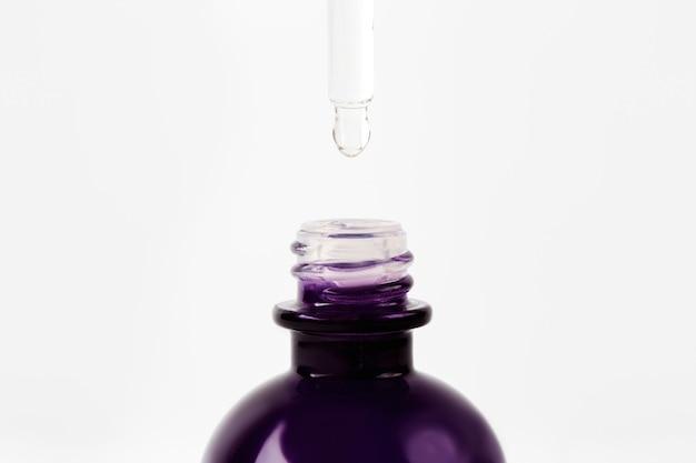 Ätherisches öl oder serum tropft von der pipette in die flasche