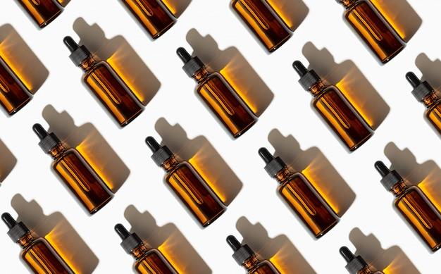 Ätherisches öl oder serumglasflaschenmuster lokalisiert auf weißem hintergrund. speicherplatz kopieren