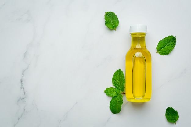 Ätherisches pfefferminzöl in der flasche mit frischer grüner pfefferminze
