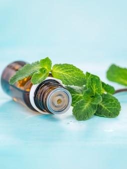Ätherisches pfefferminzöl in einer kleinen braunen flasche mit frischer grüner minze auf blauem holzhintergrund. selektiver fokus, flacher dof. speicherplatz kopieren. vertikale