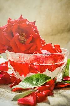 Ätherisches rosenöl in einem kleinen glas. selektiver fokus