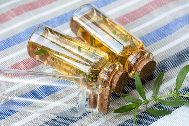 Ätherisches thymianöl in glasflaschen und einem zweig thymian. zwei fläschchen mit öl und eine leere menage