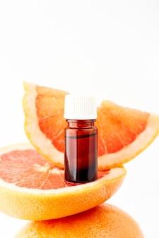 Ätherisches zitrus- oder grapefruitöl in glasflasche mit frischer grapefruit auf weißer oberfläche