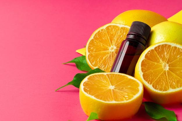 Ätherisches zitrusöl. geschnittene zitrusfrucht- und aromaflaschen auf rosa