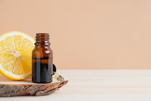 Ätherisches zitrusöl und zitronenfrucht auf holzständer auf holz und hellorangefarbenem hintergrund