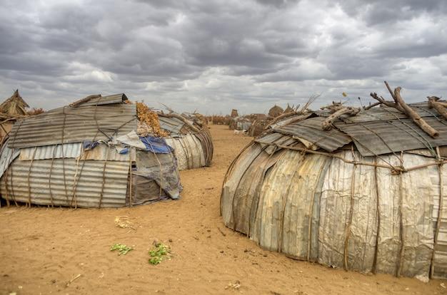 Äthiopien omo valley stämme. schrotthäuser aus metall cha und zweige aus getrockneten büschen der stämme des tals der omo-grenze zum tschad. äthiopien omo-tal-stämme.