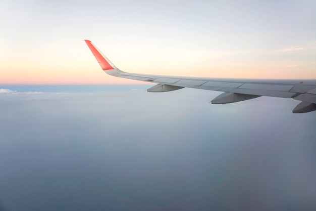 Äußere fensteransicht des flugzeuges mit flugzeugflügel und himmel des sonnenunterganghintergrundes