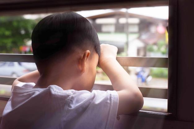 Äußeres fenster des traurigen kleinen jungen sitzende ansicht