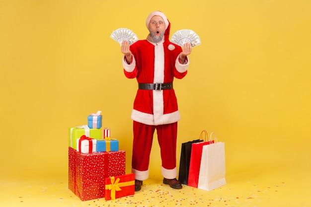 Äußerst schockierter älterer mann mit weihnachtsmann-kostüm, der einen ventilator mit geld in beiden händen hält, in der nähe von einkaufstüten und geschenkboxen steht. innenstudio erschossen auf gelbem hintergrund.