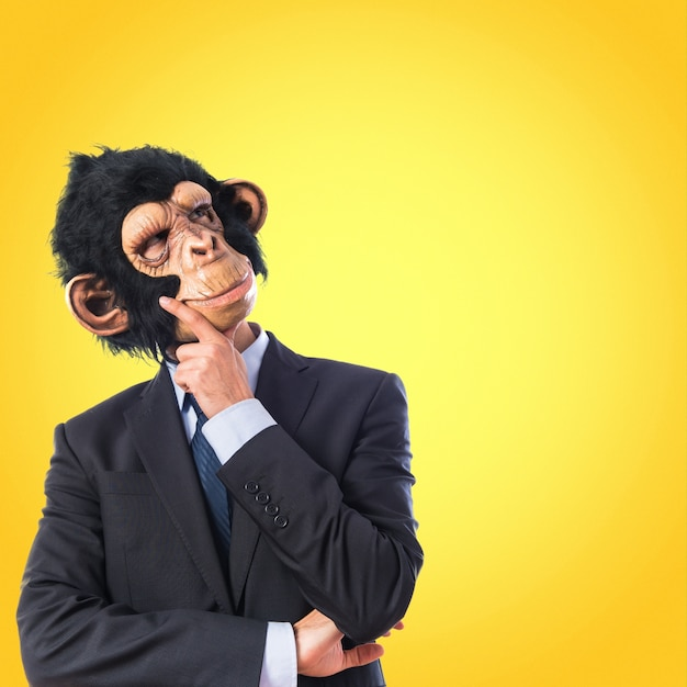Affe mann denken über weißen hintergrund auf bunten hintergrund