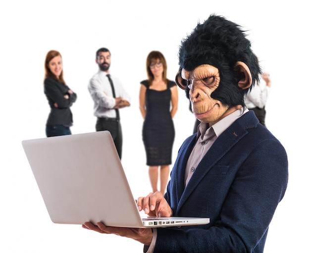 Affe mann mit laptop auf weißem hintergrund