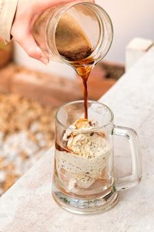 Affogato-kaffee mit eis auf einer glasschale mit weißem holztisch.