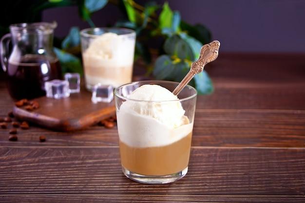 Affogato-kaffee mit eis in einem glas auf dem holztisch.