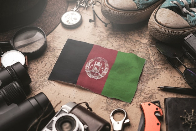 Afghanistan-flagge zwischen dem zubehör des reisenden auf alter weinlese-karte. touristisches bestimmungsort-konzept.