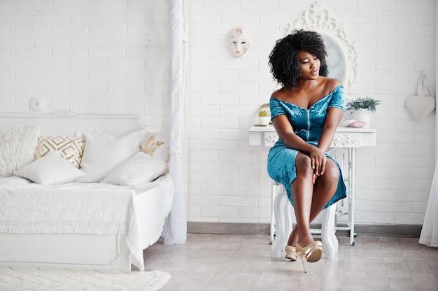 Afican amerikanische frauen im türkisfarbenen kleid der brillanten glitzer-pailletten, das auf stuhl im weißen raum gegen spiegel sitzt.