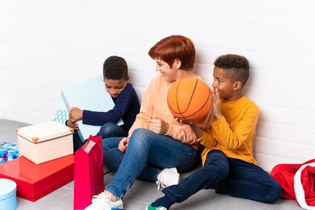 African american kinder mit ihrer mutter unter vielen geschenken für weihnachten und neujahr