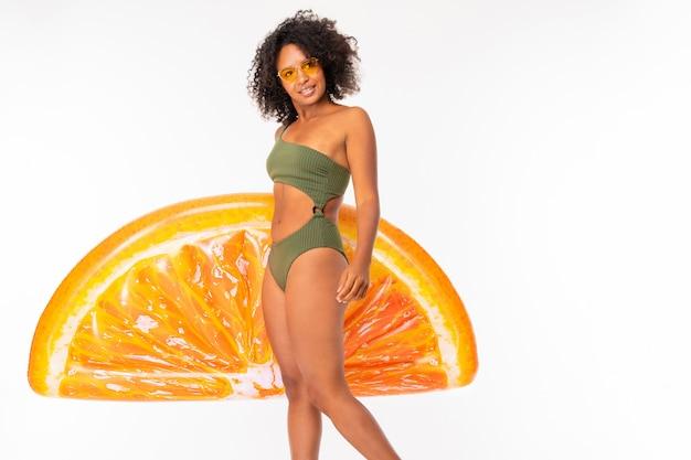 Afrikaner in einem grünen badeanzug und brille hält eine schwimmmatratze